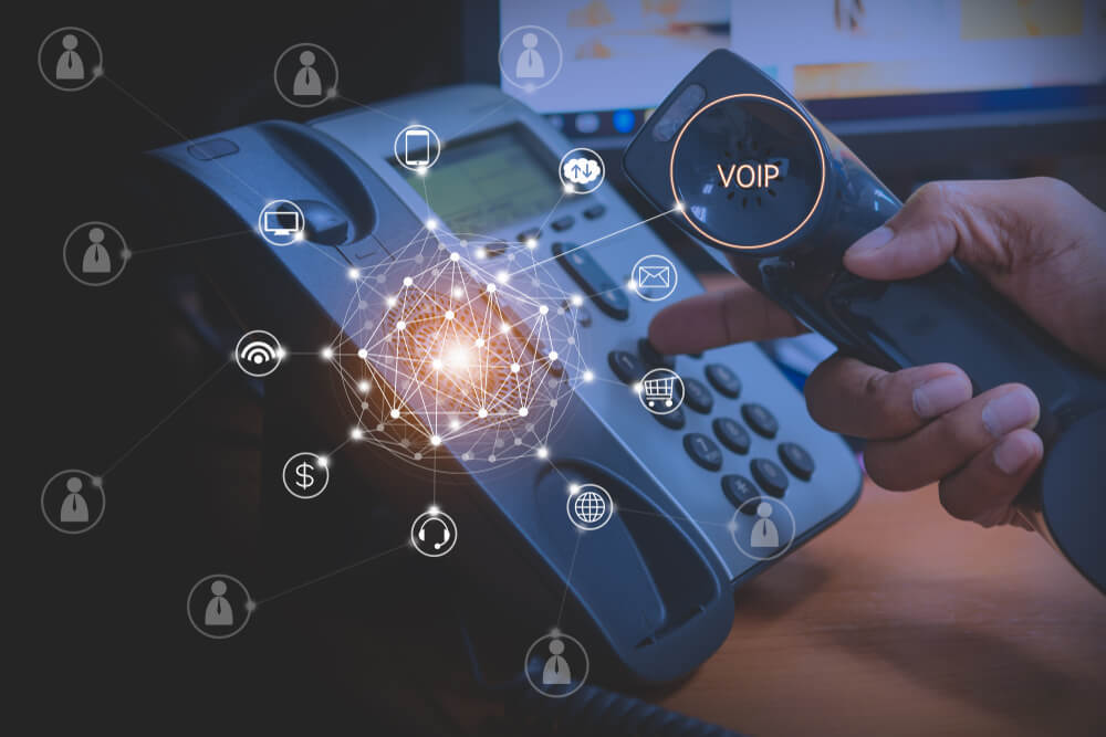 Hand of Man Using Ip Phone With Flying Icon of VoIP Services