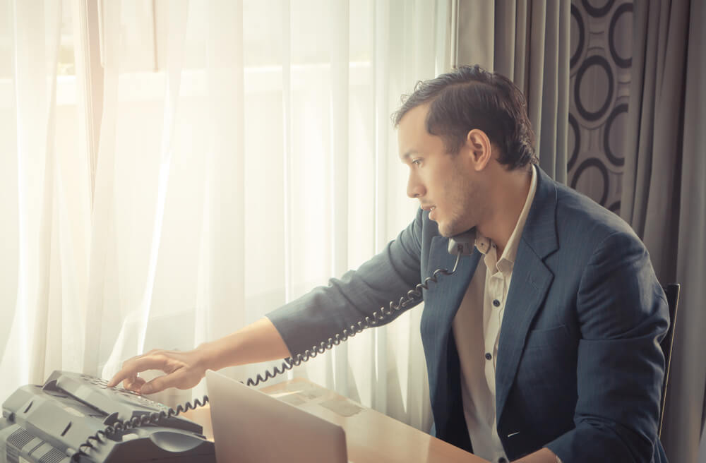 Business Man Is Making Call on Fax Machine Landline on Office Desk for Business Communication Concept.